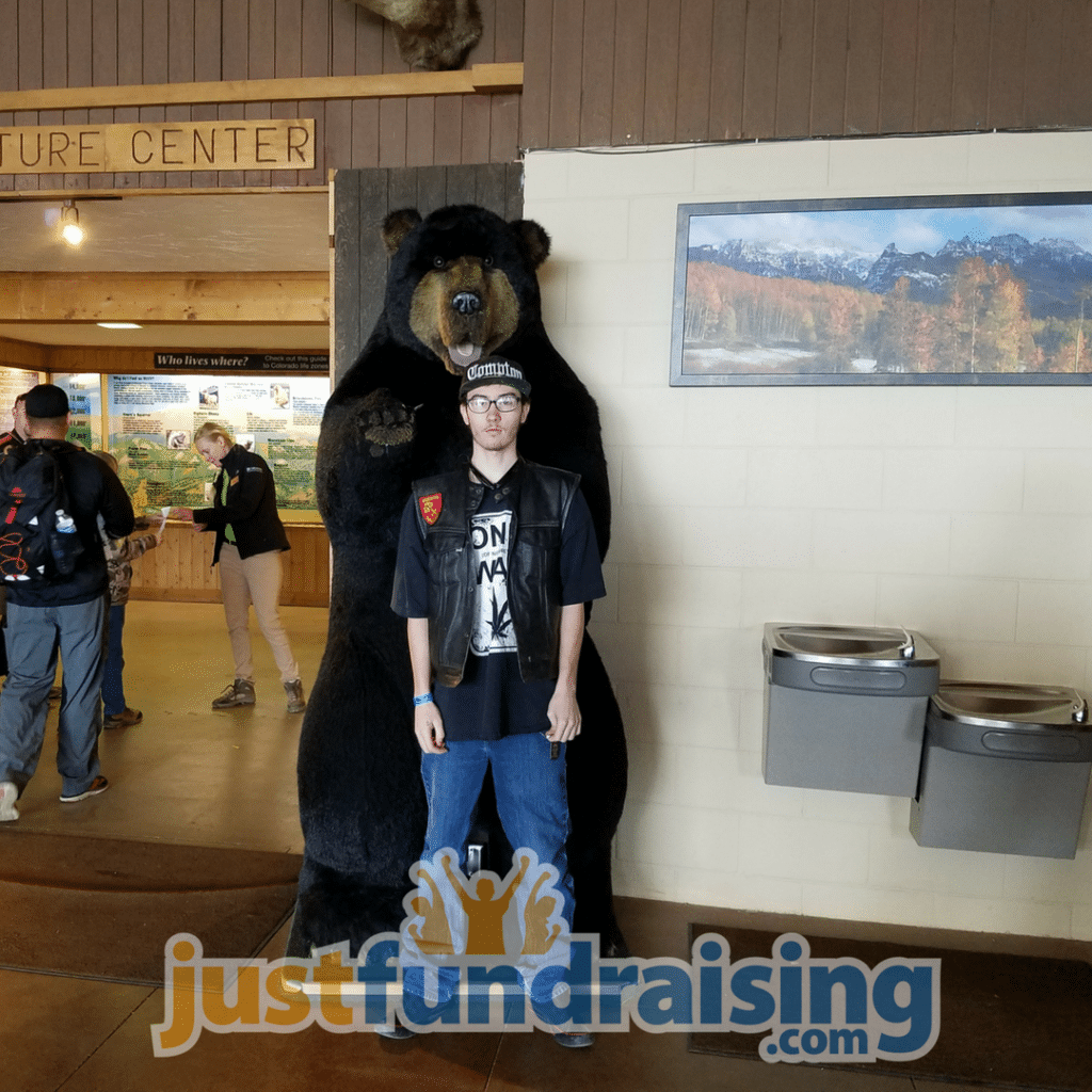 person doing the fundraiser next to a bear
